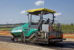 Paving work. Heavy equipment paving new road Royalty Free Stock Photos