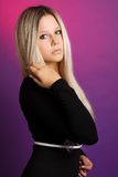 Beautiful blonde in the studio. Portrait of beautiful blonde in a black shirt and black vest in the studio, on a purple background, fashion photography Royalty Free Stock Photography