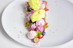 Pavlova | Basil Ice Cream | Blåbärmaräng | Jordgubbemarshmallower Arkivbild