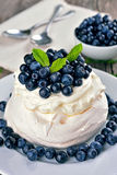 Pavlova cake with blueberries. On rustic table Royalty Free Stock Photos