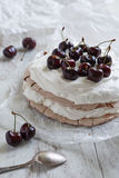 Pavlova cake with fresh cherries on the top. Pavlova cake with fresh cherries and cream on the top and a dessert spoon in the foreground Royalty Free Stock Photo