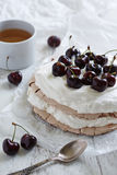 Pavlova cake with fresh cherries on the top. Pavlova cake with fresh cherries and cream on the top and a dessert spoon in the foreground Royalty Free Stock Photography
