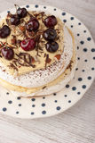 Pavlova cake with fresh cherry on the ceramic plate vertical Royalty Free Stock Images