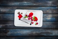 Pavlova cake with fresh raspberries on a white plate with rose petals. Top view. Beautiful wooden background. Pavlova cake with fresh raspberries on a white Royalty Free Stock Image