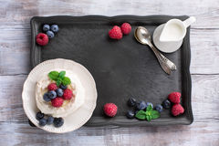 Pavlova cake with fresh summer berries. Meringue Pavlova cake with fresh raspberry and blueberry on a white rustic wooden background, top view Royalty Free Stock Images