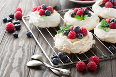 Pavlova cake with fresh summer berries. Meringues Pavlova cakes with fresh raspberry and blueberry on dark rustic wooden background, selective focus Stock Images