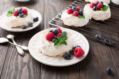 Pavlova cake with fresh summer berries. Meringues Pavlova cakes with fresh raspberry and blueberry on dark rustic wooden background, selective focus Royalty Free Stock Photos
