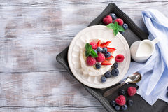 Pavlova cake with fresh summer berries. Meringues Pavlova cakes with fresh raspberry and blueberry on a white rustic wooden background, top view Stock Images