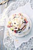 Pavlova hecho en casa con las frutas frescas y el coco; Apelmácese con los arándanos, las fresas, las uvas, las frambuesas y el c imagen de archivo libre de regalías