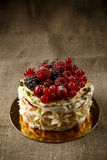 Pavlova, a home made cake from layers of meringue, whipped cream, and fresh berries Stock Photo