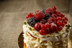 Pavlova, a home made cake from layers of meringue, whipped cream, and fresh berries Stock Image