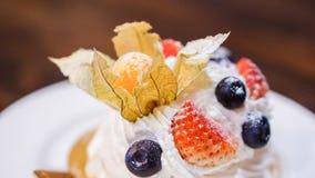 Pavlova kaka med bär och kräm på tabellen royaltyfria foton