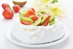 Pavlova kaka med kiwin och jordgubben Arkivfoton