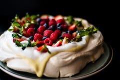 Pavlova kaka med tonkakräm och bär Arkivfoton