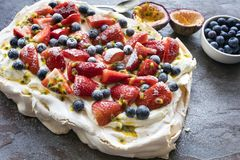 Pavlova Meringue Cake with Berries and Passionfruit. Side view on slate stock photography