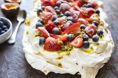 Pavlova Meringue Cake with Berries and Passionfruit Top View. Pavlova meringue cake with berries and passionfruit. Side view on slate royalty free stock photography