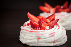 Pavlova meringue cake decorated with fresh strawberry on black Stock Photography