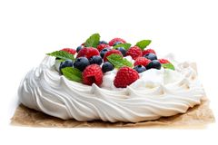 Pavlova meringue nest with berries and mint leaves isolated on white. Pavlova  meringue nest with berries and mint leaves isolated on white stock photography