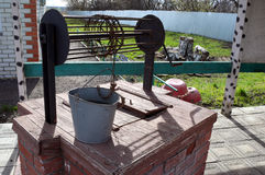 PAVLOVSK, RUSSIA - 23 APRILE 2017: il secchio del metallo è bene sulla copertura di questo con acqua potabile Fotografie Stock