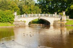 Visconti bridge across Slavyanka River and tourists walking along in Pavlovsk, St Petersburg, Russia. PAVLOVSK, RUSSIA - SEPTEMBER 21, 2017. Visconti bridge Stock Image