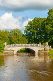 Pavlovsk, St Petersburg, Russia. Visconti bridge across Slavyanka River and tourists walking along. PAVLOVSK, RUSSIA - SEPTEMBER 21, 2017. Visconti bridgeacross Royalty Free Stock Image