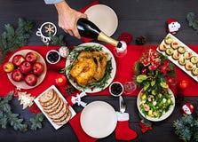 Pavo cocido Cena de la Navidad La tabla de la Navidad se sirve con un pavo, adornado con malla y velas brillantes frito foto de archivo