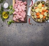 Pavo crudo con la salsa de tomate, pimienta, especias, ingredientes de las hierbas para el guisado en cierre rústico de madera de Foto de archivo