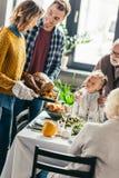 pavo que lleva del hombre y de la mujer para la cena de la acción de gracias mientras que mirada emocionada de la familia imagenes de archivo