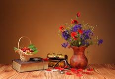 Pavot rouge dans un vase, un livre et des cerises Photographie stock