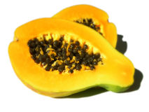Paw paw. Orange paw paw fruit cut in half showig all its seeds Stock Image