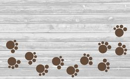 Paw prints trail on wooden background stock photo