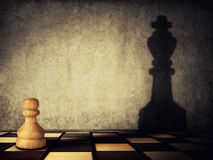 Pawn aspiration. Pawn chess piece casting a shadow of a king on a concrete wall. Business aspirations and leadership concept. Magical transformation Royalty Free Stock Images