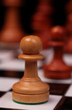 Pawn on chess board. Light colored wooden chess pawn in sharp focus with dark pieces out of focus across the chess board Royalty Free Stock Image