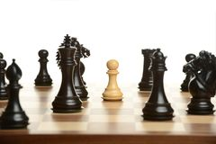 Pawn chess pawn surrounded by black opponents Royalty Free Stock Photography