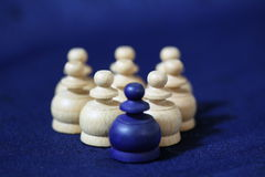 Blue pawn. A close up of white chess pieces in a group, with a single blue pawn at the front on a blue background Royalty Free Stock Photos