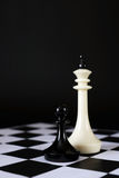 Pawn contra of enemy king. Unequal fight. Concept with chess pieces against black background Royalty Free Stock Photography