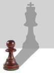 The pawn creates a shade in the form of the king. Chess Pawn creating a shade that is looking like the king Royalty Free Stock Images