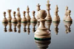 Pawn in front. Light colored, wooden pawn in front of other chess pieces Stock Photo