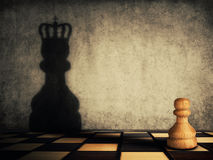 Pawn glorification. Pawn chess piece glorification, casting a shadow of coronation on a concrete wall. Business aspirations and leadership concept. Magical Royalty Free Stock Photography