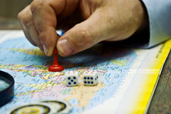 A pawn in a man`s hand on a geographical map of the world against a background of a magnifying glass Stock Images