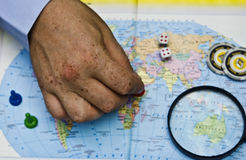 A pawn in a man`s hand on a geographical map of the world against a background of a magnifying glass and playing chips Royalty Free Stock Image