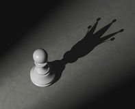 Pawn with shadow of the king Royalty Free Stock Images