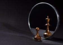 Pawn som ser i spegeln och ser en konung Arkivbild
