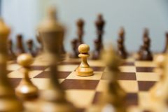 Pawn standing in the middle of chess board. Courage and leadership concept. royalty free stock photos