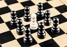 Pawn surrounded by enemies. A white pawn surrounded by black pawns Stock Image