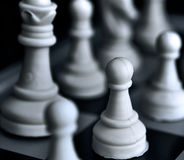 Pawn of white figures on a chessboard against a dark background. Stock Images