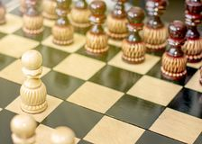Pawn on a wooden chessboard. Game of chess