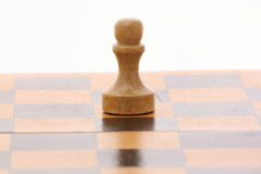 Pawn on a wooden chessboard Stock Photography