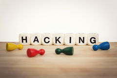 Pawns around the word hacking spelled by toy dice Royalty Free Stock Photos