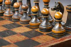 Pawns on chessboard. Vintage wooden black chess pieces on chessboard with focus on pawns Royalty Free Stock Photography